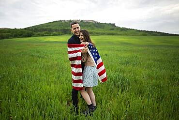 Smiling young couple wrapped in American flag in wheat field