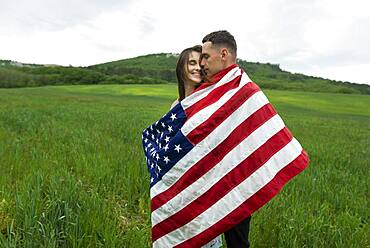 Young couple wrapped in American flag in wheat field