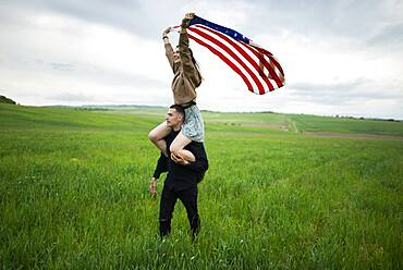 Young couple with American flag in wheat field
