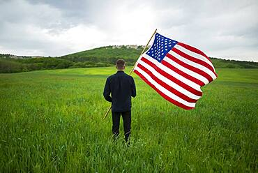 Rear view of man with American flag in wheat field
