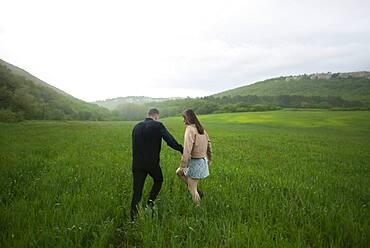 Rear view of young couple walking in wheat field in rain