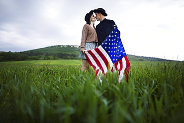 Young couple with American flag kissing in wheat field