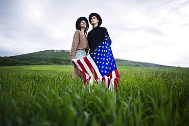 Young couple holding American flag in wheat field