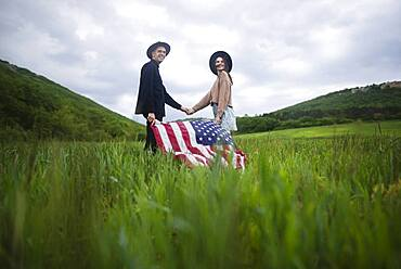 Young couple with American flag holding hands in wheat field