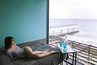 Woman reclining on bed in hotel with view on sea
