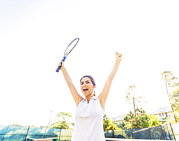 Portrait of young woman holding tennis racket, raising arms in celebration, Jupiter, Florida