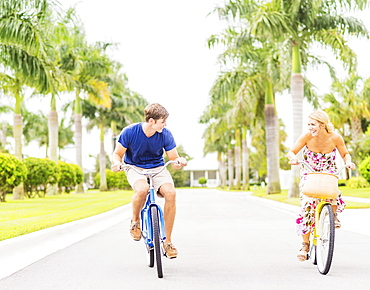 Young couple driving bicycles along street with palm trees, Jupiter, Florida