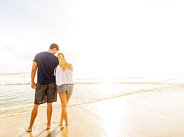 Rear view of young couple standing side by side on sandy beach, looking at sea, Jupiter, Florida
