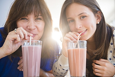 Portrait of mother and daughter (14-15) drinking milkshakes