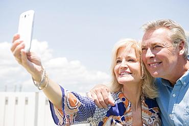 Portrait of couple posing for smartphone selfie