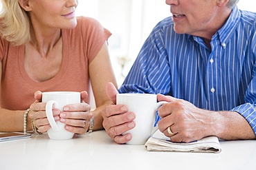 Cropped shot of husband and wife drinking coffee and talking