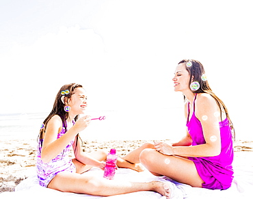 Mom and her daughter (6-7) sitting on blanket on beach, Jupiter, Florida