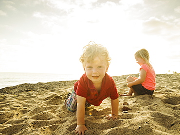 Girl (4-5) and boy (2-3) playing on beach, San Clemente, California
