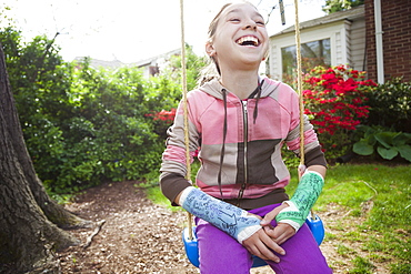 Smiling girl (12-13) with two arm casts sitting in tree swing