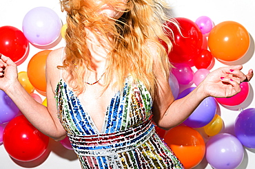 Woman dancing in front of balloon wall