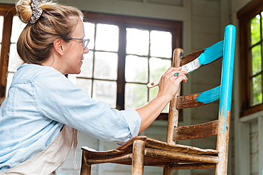 Woman painting old wooden chair