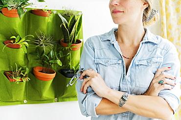 Woman standing by vertical garden
