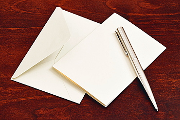 Envelope and pen on wooden table