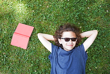 Boy lying in grass smiling with book