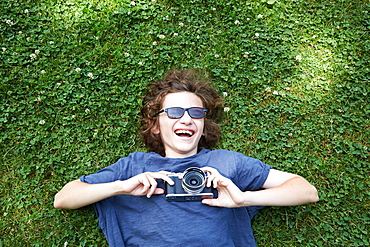 Boy lying in grass with camera