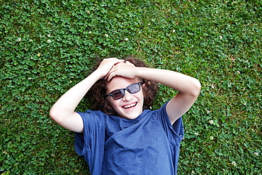 Boy lying in grass and laughing