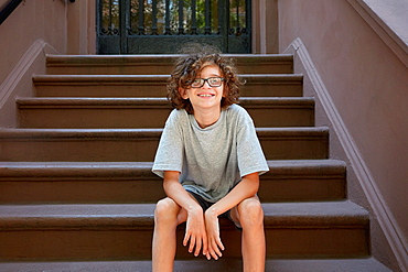 USA, New York, New York City, Boy sitting on steps in front of building