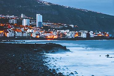 Spain, Canary Islands, Tenerife, Puerto De La Cruz, Buildings on sea coast at dusk