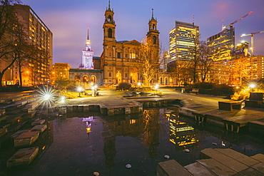 Poland, Masovia, Warsaw, Church and illuminated city skyscrapers reflecting in pond at night