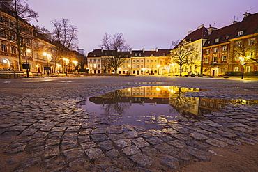 Poland, Masovia, Warsaw, Illuminated town square reflecting in puddle at night