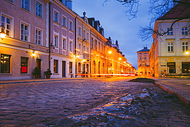Poland, Masovia, Warsaw, Townhouses along cobblestone street in old town at night