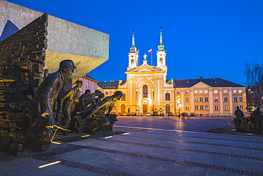 Poland, Masovia, Warsaw, Town square with World War II monument and illuminated cathedral