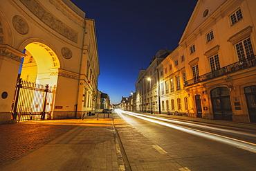 Poland, Masovia, Warsaw, Illuminated city street with historical buildings at night