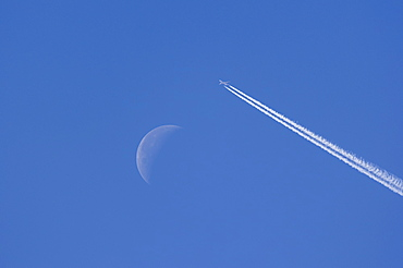 Airplane leaving contrails against blue sky with waning moon
