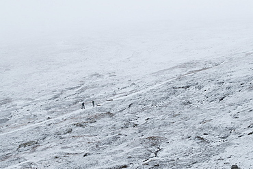 Australia, New South Wales, Snowy mountain landscape at Charlotte Pass in Kosciuszko National Park with incidental people on trail