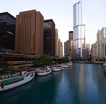 Usa, Illinois, Chicago, Downtown buildings and boats moored by river at dawn
