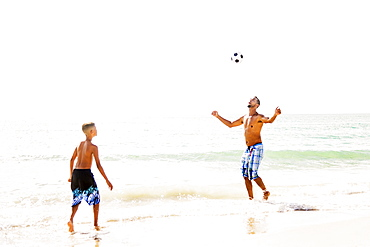 Father and son (10-11) playing soccer on beach