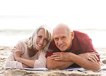 Senior couple lying on beach