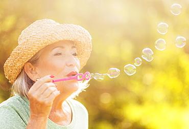 Senior woman blowing soap bubbles