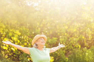 Senior woman in park with arms outstretched