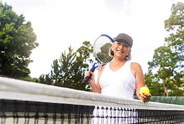 Portrait of senior woman on tennis court, Jupiter, Florida
