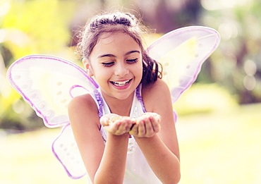 girl (8-9) holding fairy dust in hands