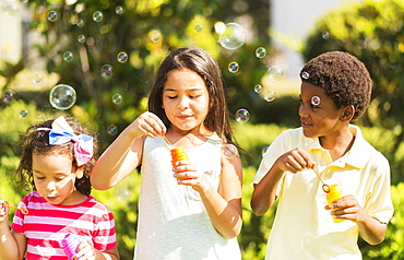 Girls( 4-5, 8-9) and boy (6-7) blowing soap bubble