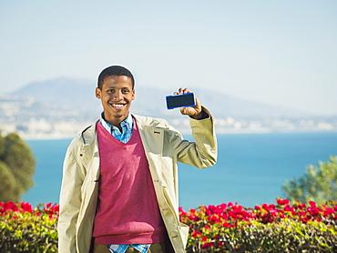 Portrait of smiling man holding smartphone, Dana Point, California
