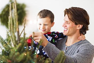 Man with kid (6-7) decorating Christmas tree