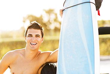 Young man holding surfboard, Jupiter, Florida, USA