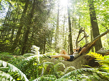 Young woman lying down on log, USA, Oregon, Portland