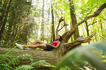 Young woman lying down on log in forest, USA, Oregon, Portland