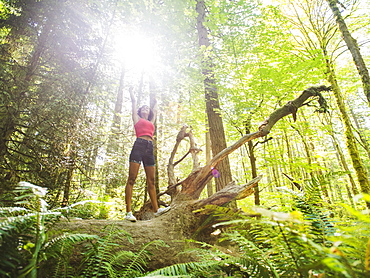 Young woman standing on log in forest, USA, Oregon, Portland