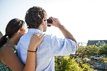 Rear view of couple, man looking through binoculars, USA, Washington, Everett