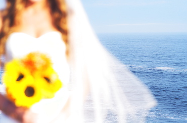 Mid section of bride holding sunflower bouquet, sea in background, USA, Maine, Bristol